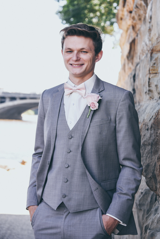 Groom leaning against a stone wall
