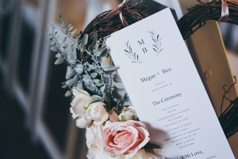 a wedding program tucked into a bouquet of roses and sprigs of greenery