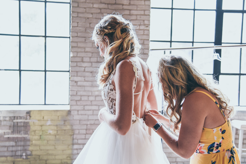 bridesmaid fastening the back of a brides wedding dress