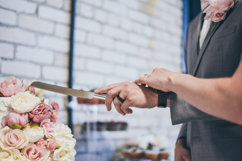 close up of bride and grooms hands while they cut their cake