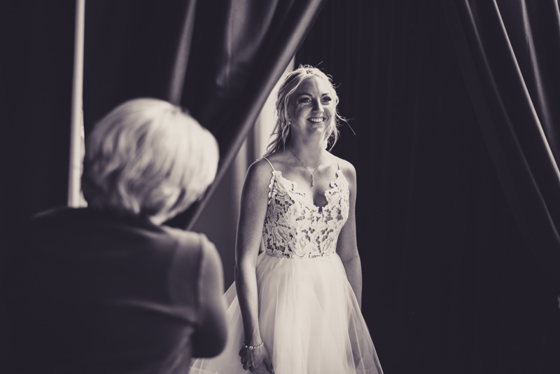 black and white image of a bride revealing herself to her bridesmaids