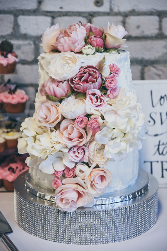 lucious wedding cake covered in buttercream frosting, roses and peonies in shades of pink and cream on a silver cake stand