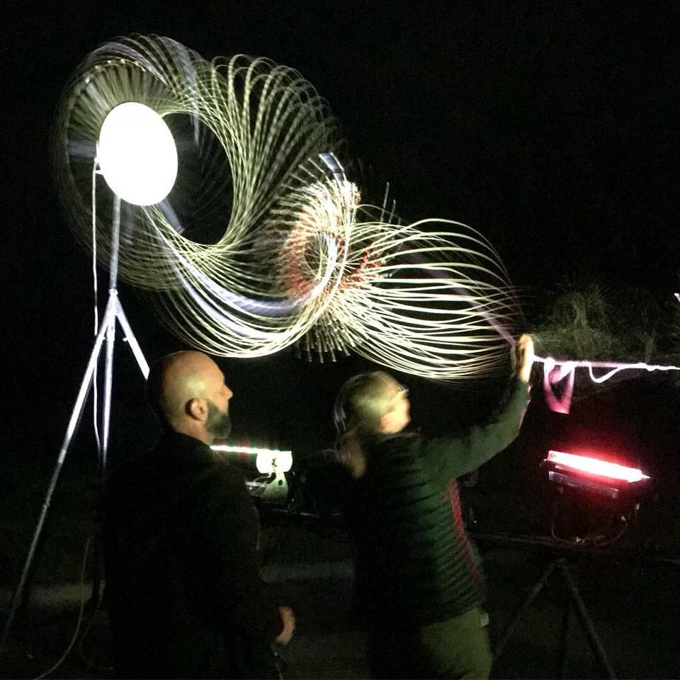 man in the dark, working on an art piece created from string and strobe lights