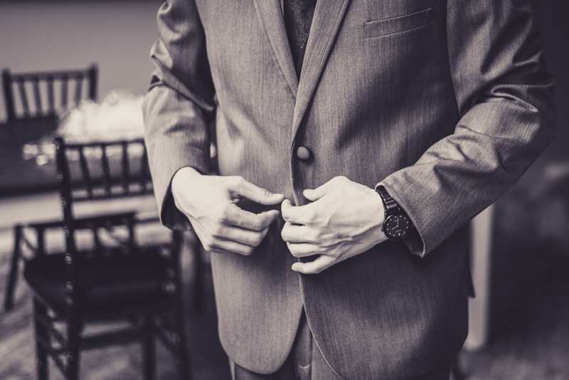 black and white image of a groom fastening his jacket