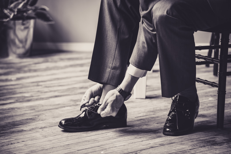 black and white image of a groom tying his shoes