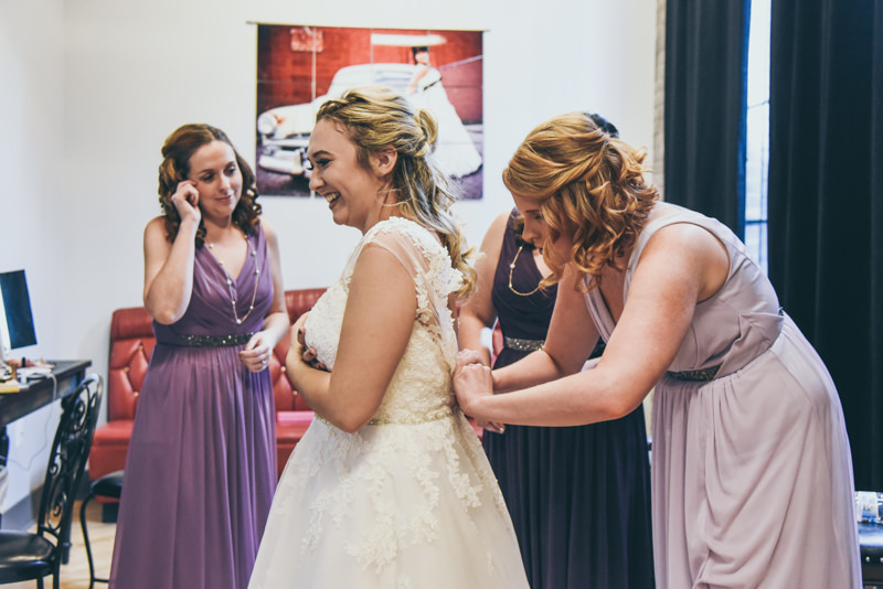 bridesmaids in purple dresses helping to fasten the back of a bride's wedding dress