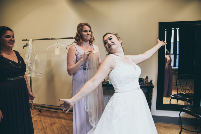 bride being silly and showing off her wedding gown after she gets dressed