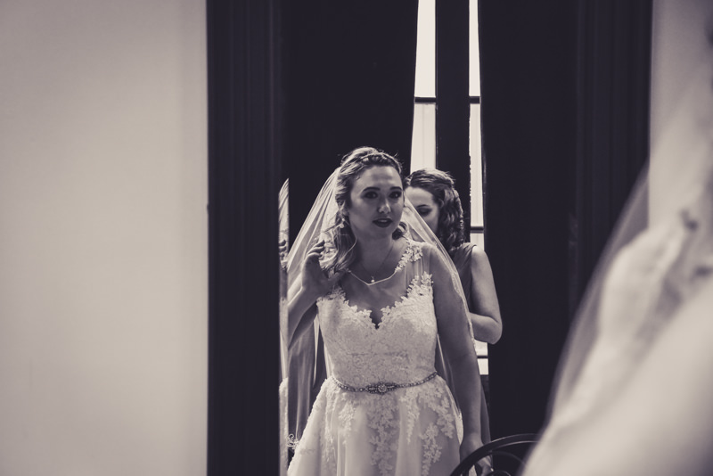 black and white image of a bride looking at herself in a mirror after getting ready for her wedding day