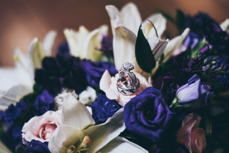 close up image of bride and groom's rings on flowers in her bouquet