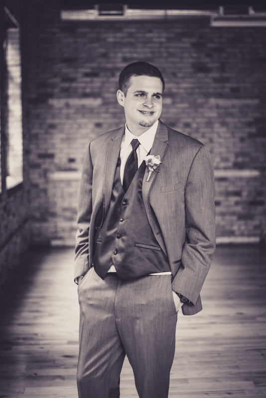 black and white image of a groom in an industrial loft