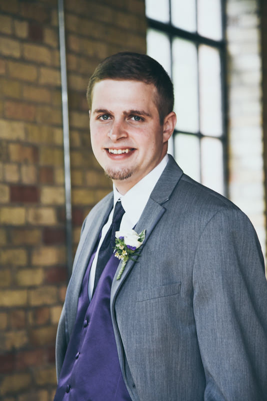 close up portrait of a groom in a gray jacket and purple vest