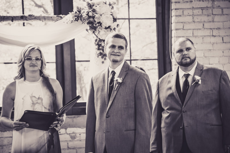 black and white image of a groom looking at his bride for the first time as she walks down the aisle