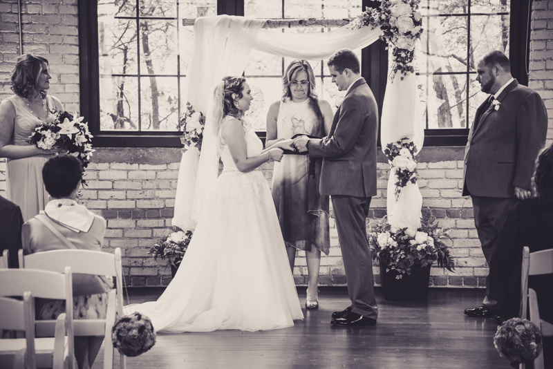 black and white image of a bride and groom exchanging rings
