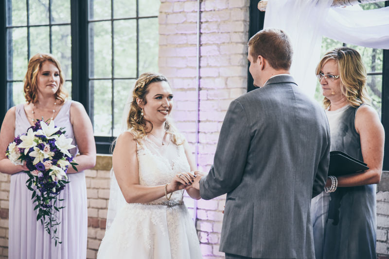 bride smiling as she puts the ring on the groom's finger