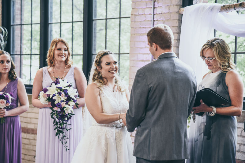 bride and groom smiling at each other during ceremony