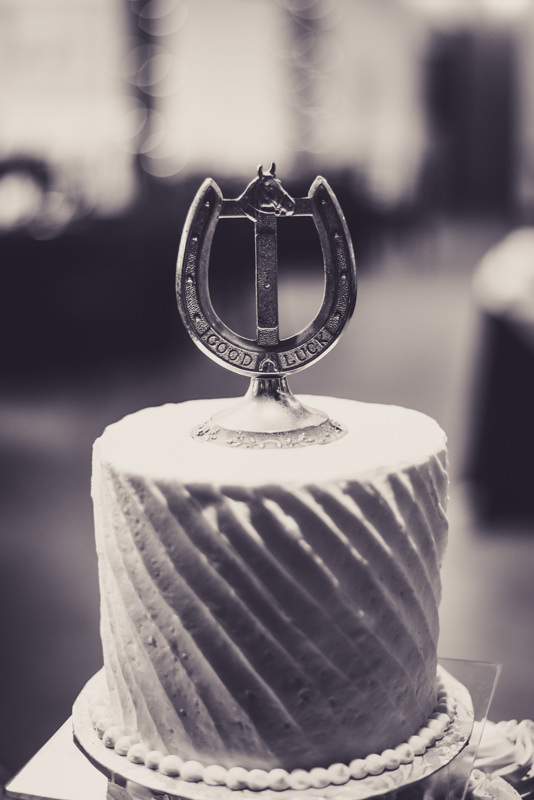 black and white photo of a wedding cake with silver horseshoe cake topper