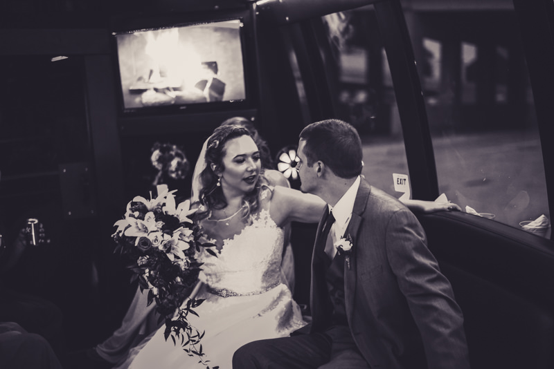black and white image of a bride and groom on the party bus