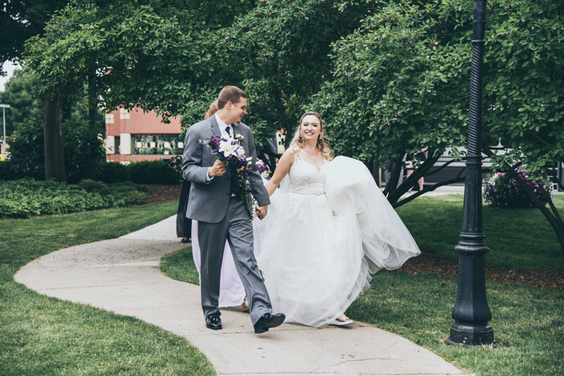 groom holding bouquet and helping the bride get to photo location