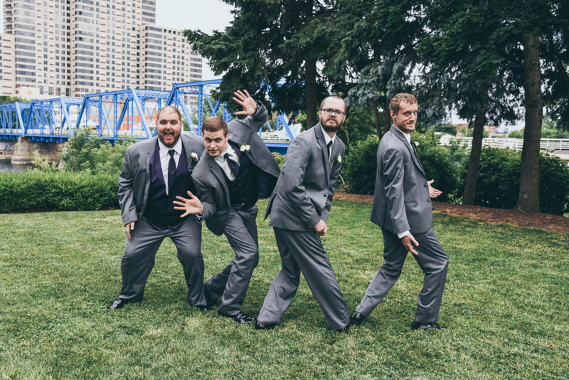 groomsmen and groom having fun in a city scene
