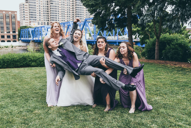 bridesmaids holding up the groom and laughing