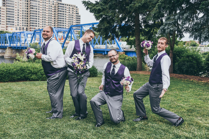 groom and groomsmen holding bouquets and being silly