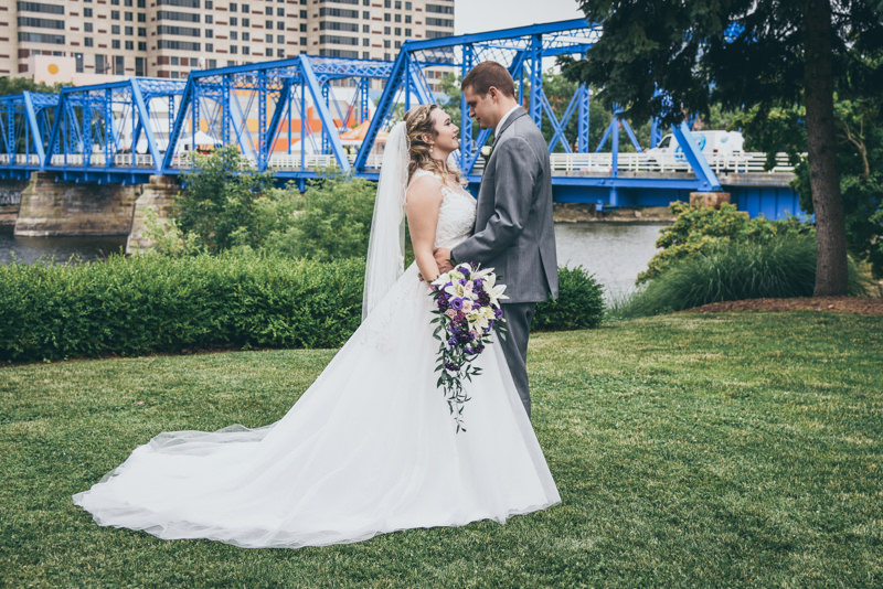bride and groom facing each other in front of the Grand Rapids skyline and Blue Bridge