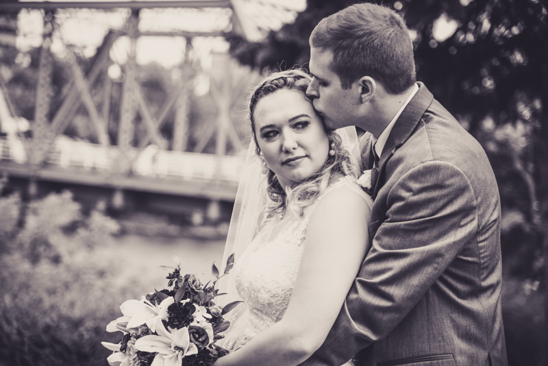 black and white image of a groom holding the bride in front of a bridge in a city