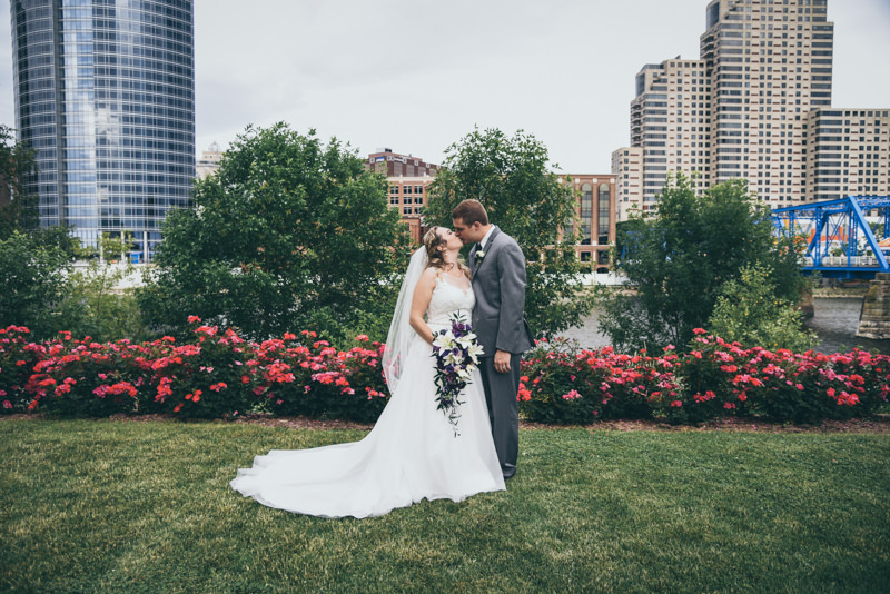 bride and groom facing each other and holding each other close in front of a row of red roses and the Grand Rapids skyline