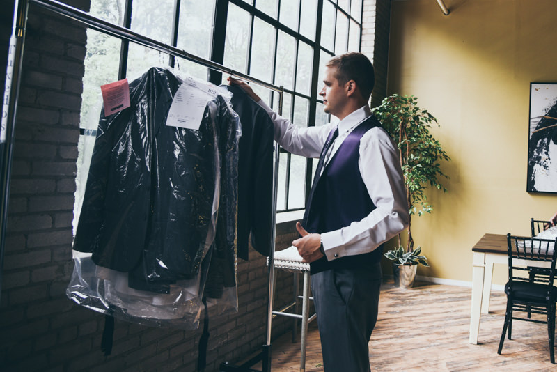 Groom taking his tuxedo off the rack to start getting ready for his wedding day