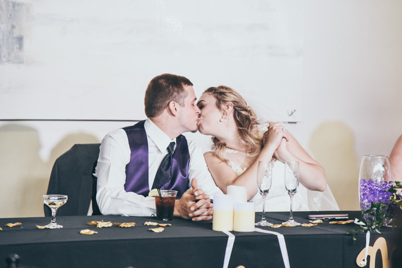 bride and groom kissing at head table during wedding reception