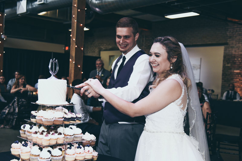 bride and groom smiling and preparing to cut their cake