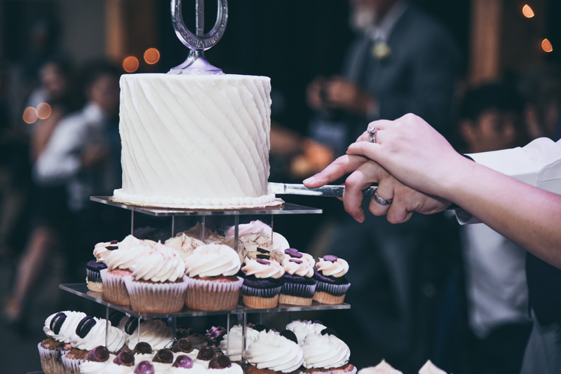 close up of the bride and groom's hands as they cut their cake