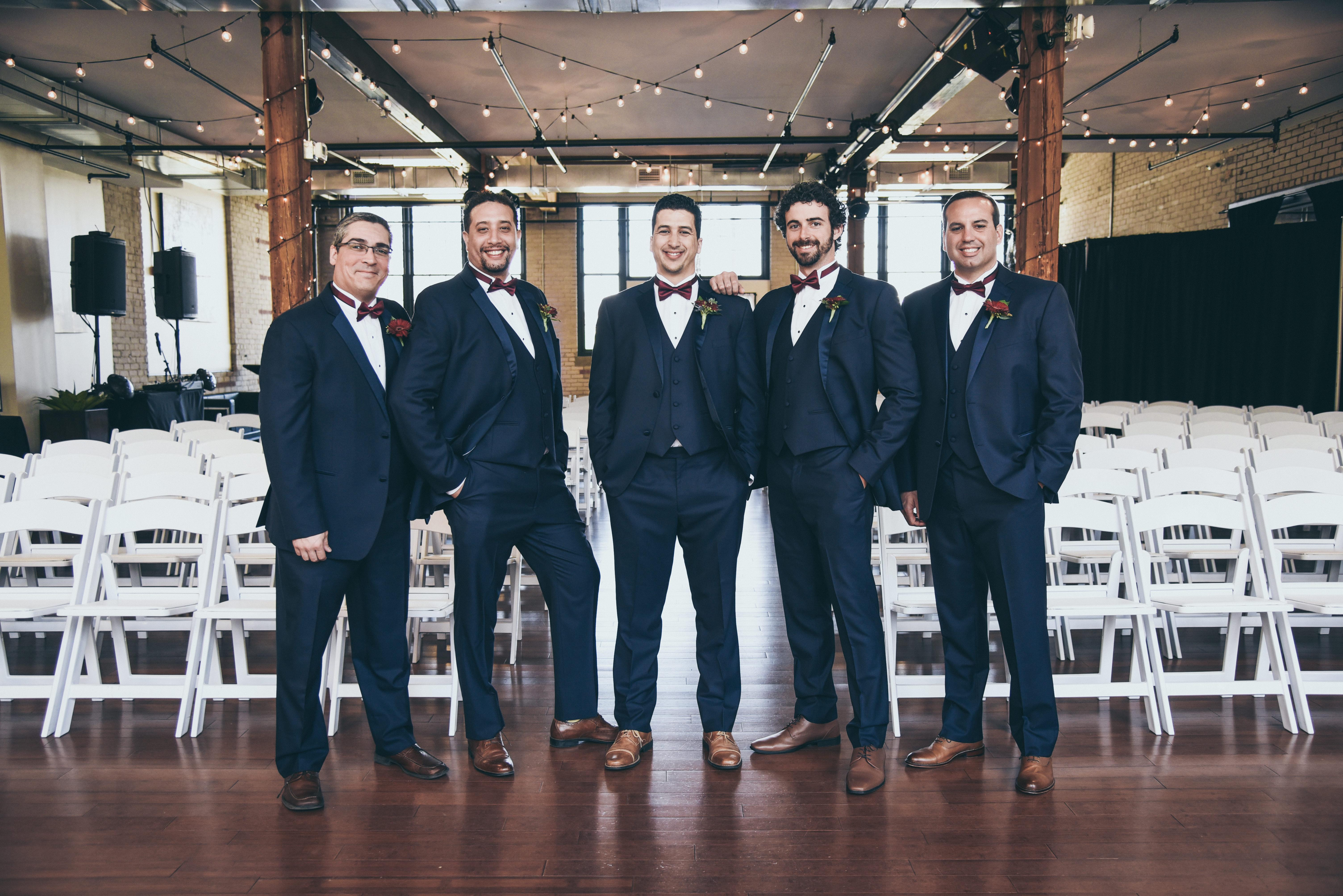 groom and groomsmen in navy tuxedos in a loft venue under bistro lights