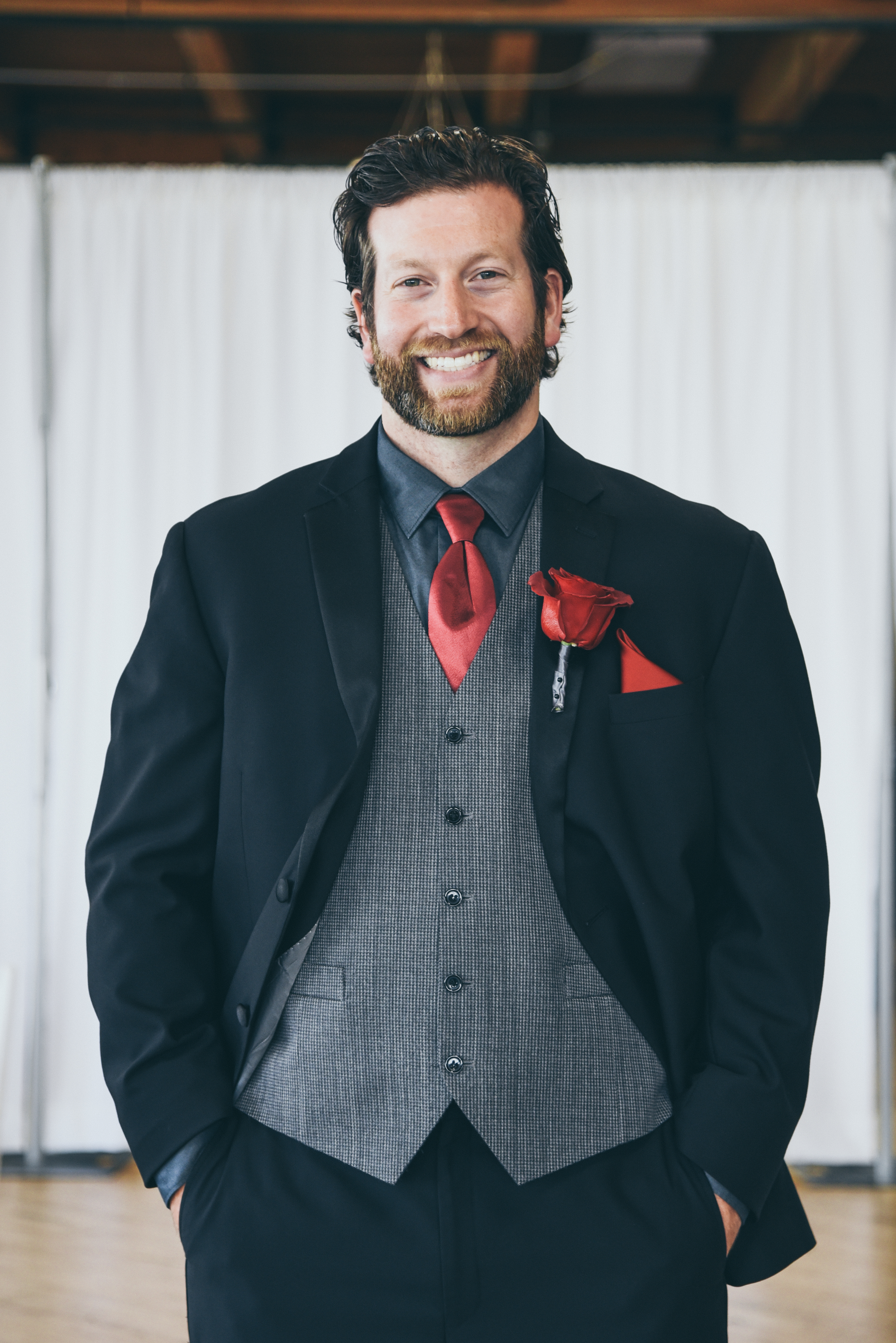 groom dressed in black, red, and gray