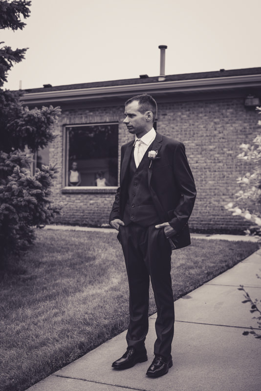 black and white image of the groom waiting for his bride during their first look