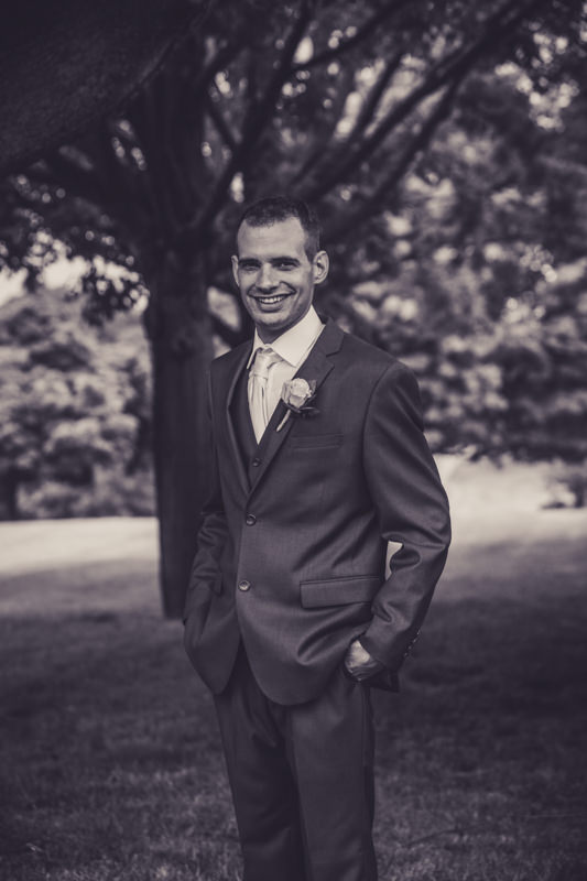 black and white image of a groom smiling during photos