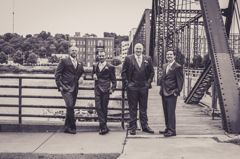 black and white image of groom and groomsmen by a bridge and river
