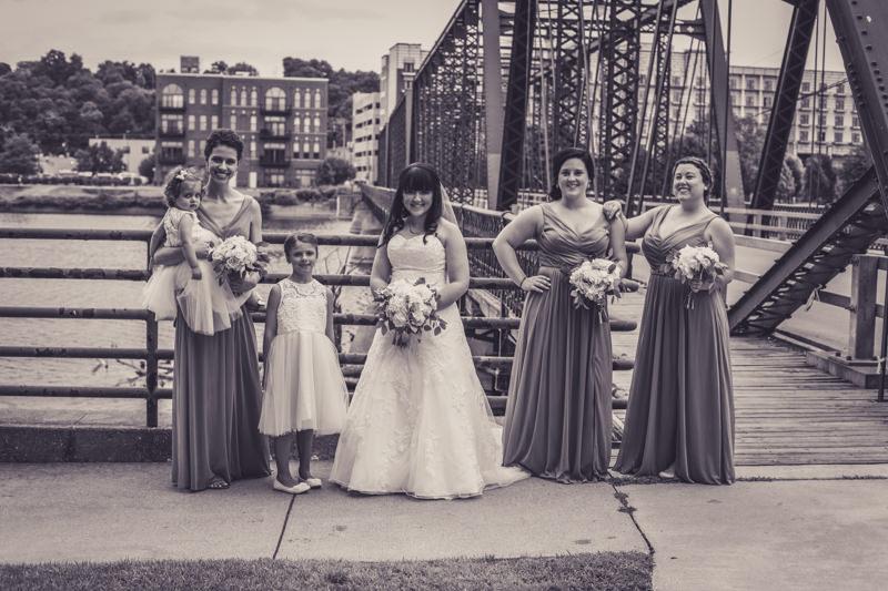 bride and bridesmaids by a bridge