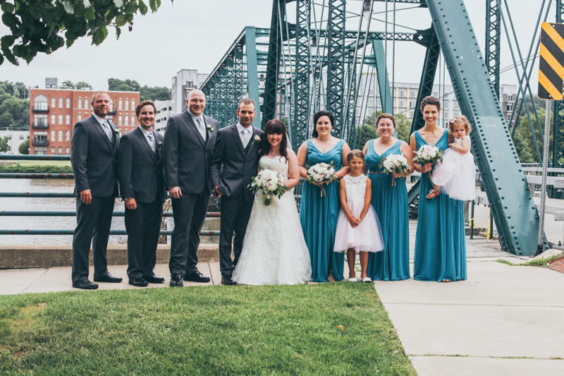 bridal party in front of a green bridge