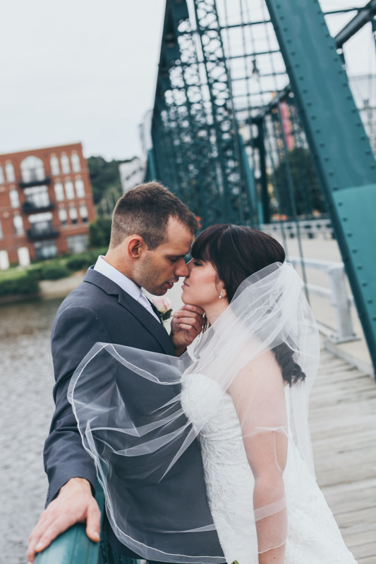 bride and groom kissing on a green bridge as the veil blows around them
