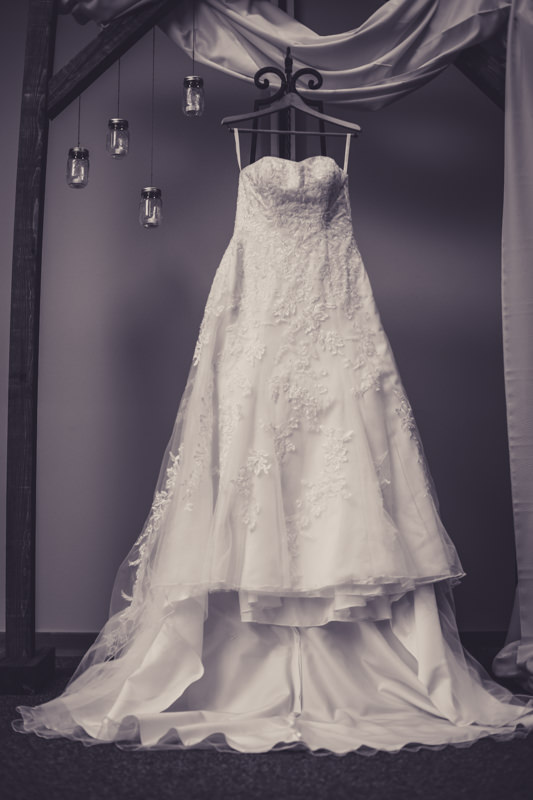 black and white image of wedding dress hanging from arbor at the altar