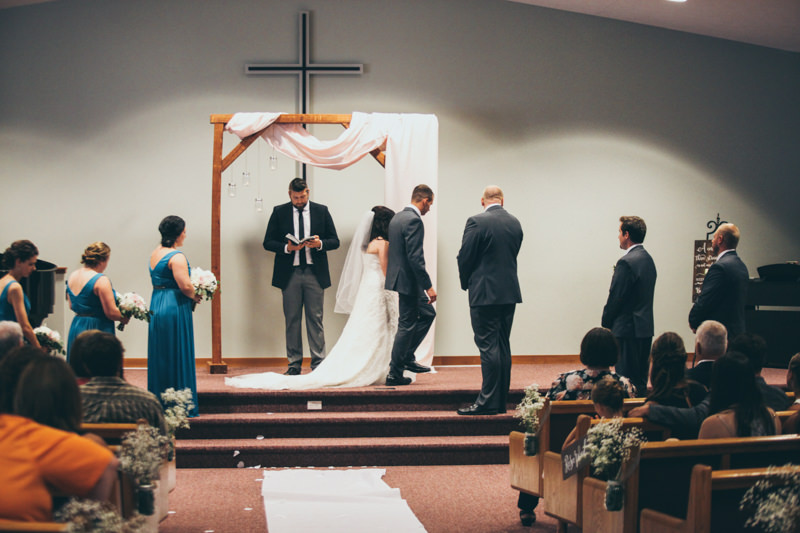 bride and groom walking across stage at church