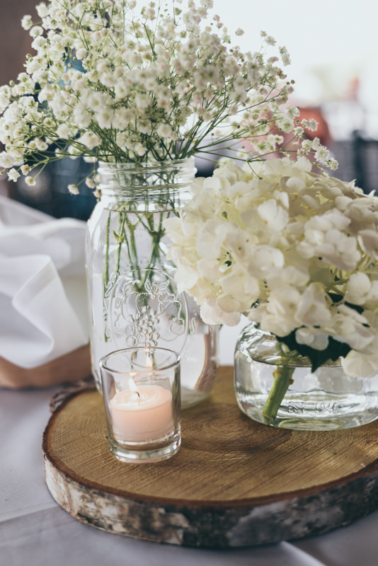 mason jars with baby's breath and wooden rounds as centerpieces at a wedding