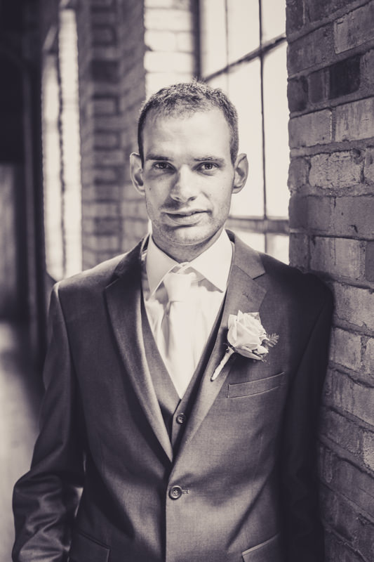 black and white image of a groom leaning on a brick wall