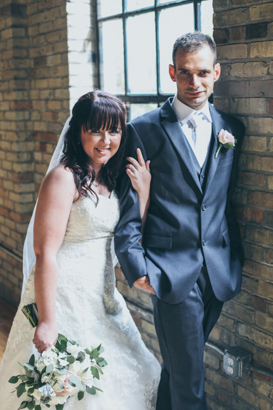 bride and groom together in a brick room