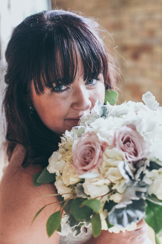 bride with her bouquet up close to her face