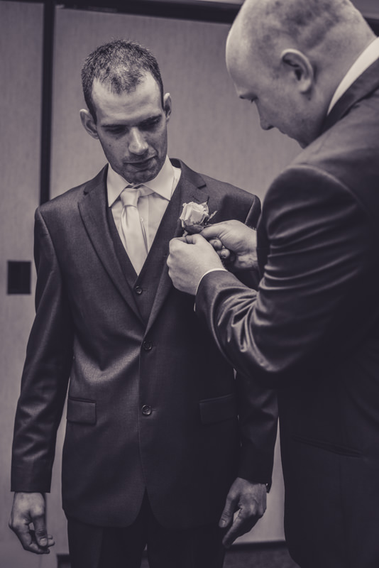 Groomsman putting on boutonniere on the groom