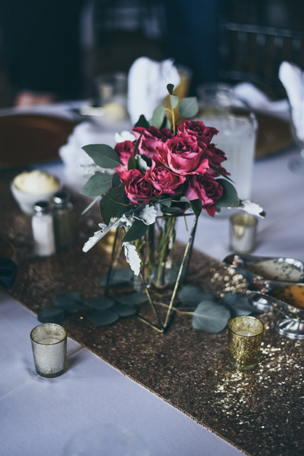 red floral centerpiece on a sequined runner at a wedding