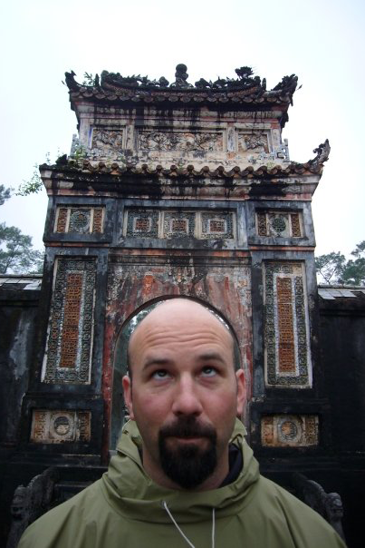 artist standing in front of a large ancient building