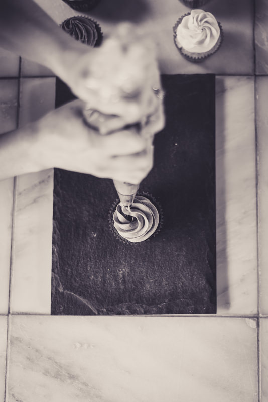 black and white image of a baker frosting a cupcake